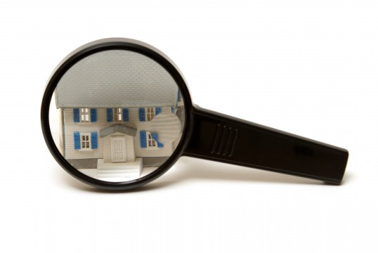 A home inspection concept using a model house and a magnifying glass.